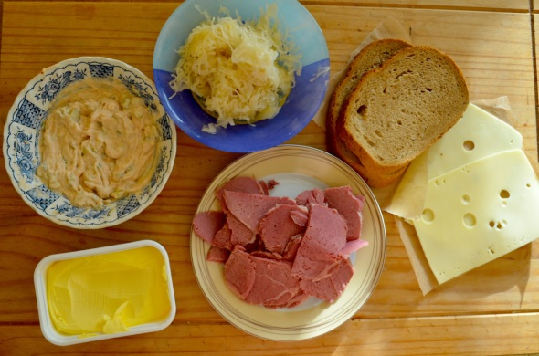All the ingredients, from left to right: Butter, Russian sauce, Sauerkraut , Sliced rye bread, Swiss cheese (emmental )and corned beef in the middle.